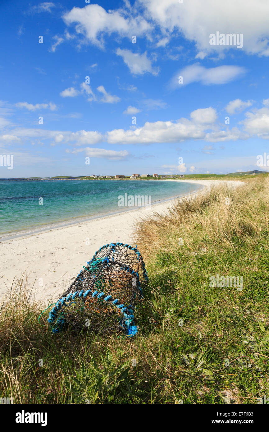 Lobster pot on sand dunes by beautiful quiet Traigh nam Faoghailean beach Balranald RSPB Nature Reserve North Uist - Stock Image
