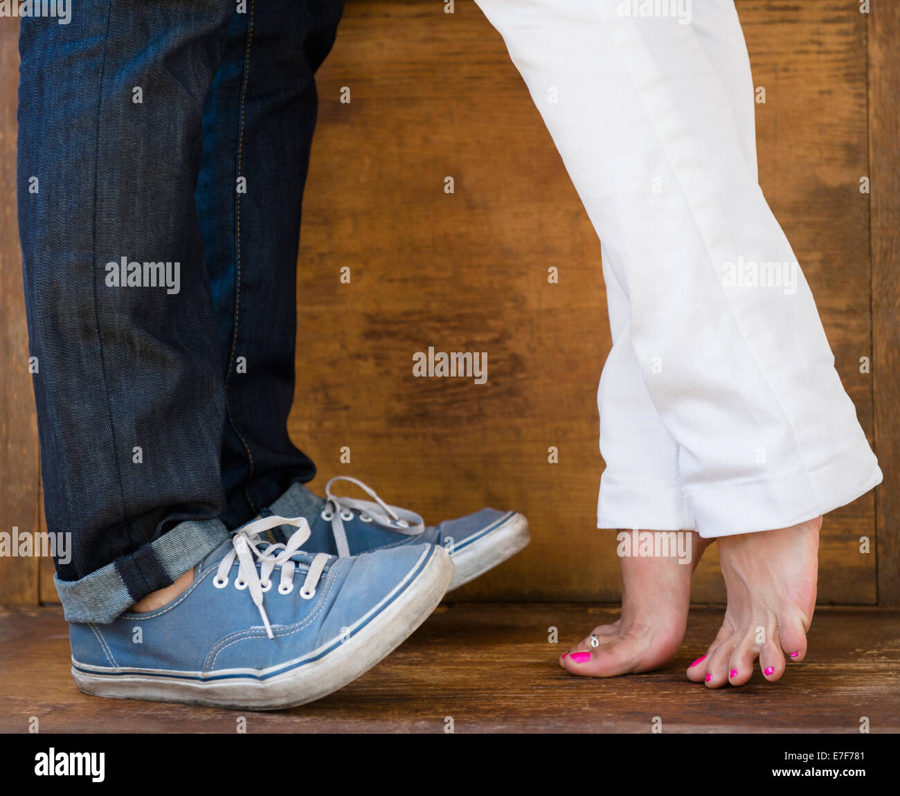 Woman standing on tiptoes to kiss boyfriend Stock Photo