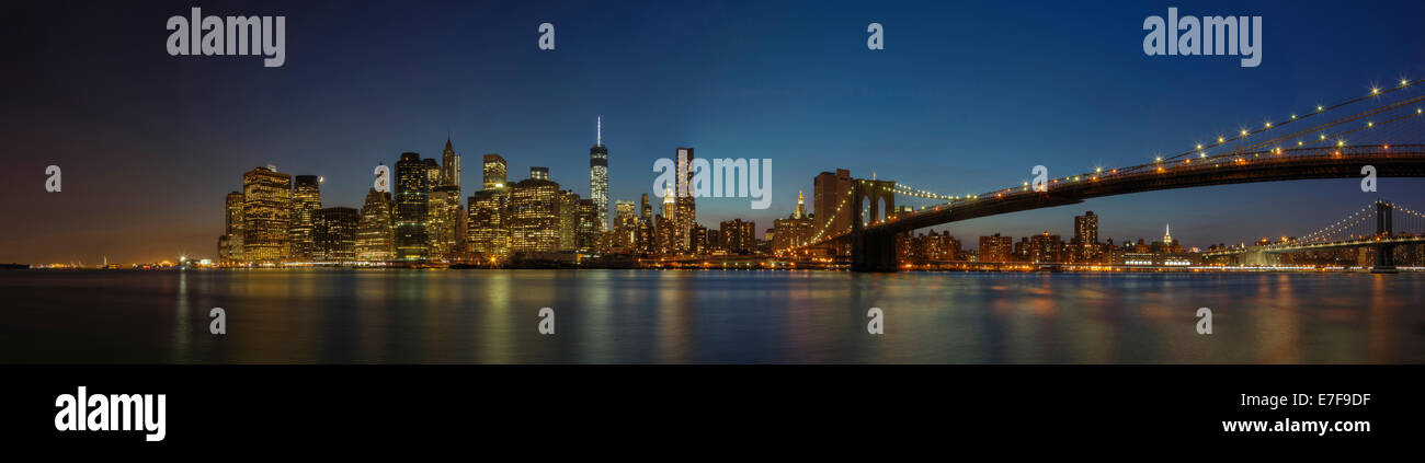 Panoramic view of New York city skyline illuminated at night, New York, United States - Stock Image