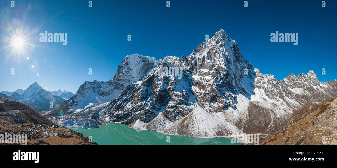 Sun rising over snowy mountains in rural landscape, Tengboche, Khumbu, Nepal - Stock Image