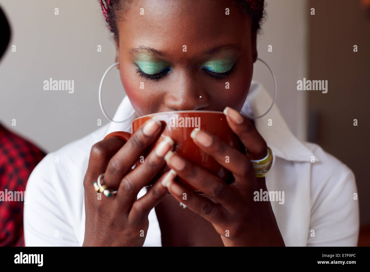 Woman drinking cup of coffee in cafe Stock Photo