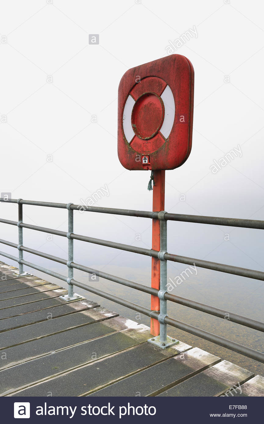 An emergency life buoy stand on a mist covered pier at Loch Lomond - Stock Image