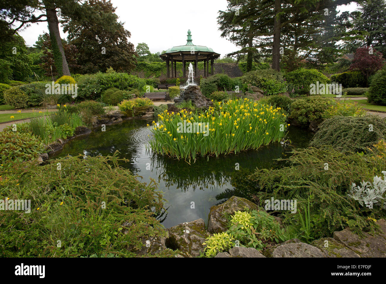 Park with bandstand, rock garden, trees, shrubs, and ornamental pond with fountain and flowering irises at village - Stock Image