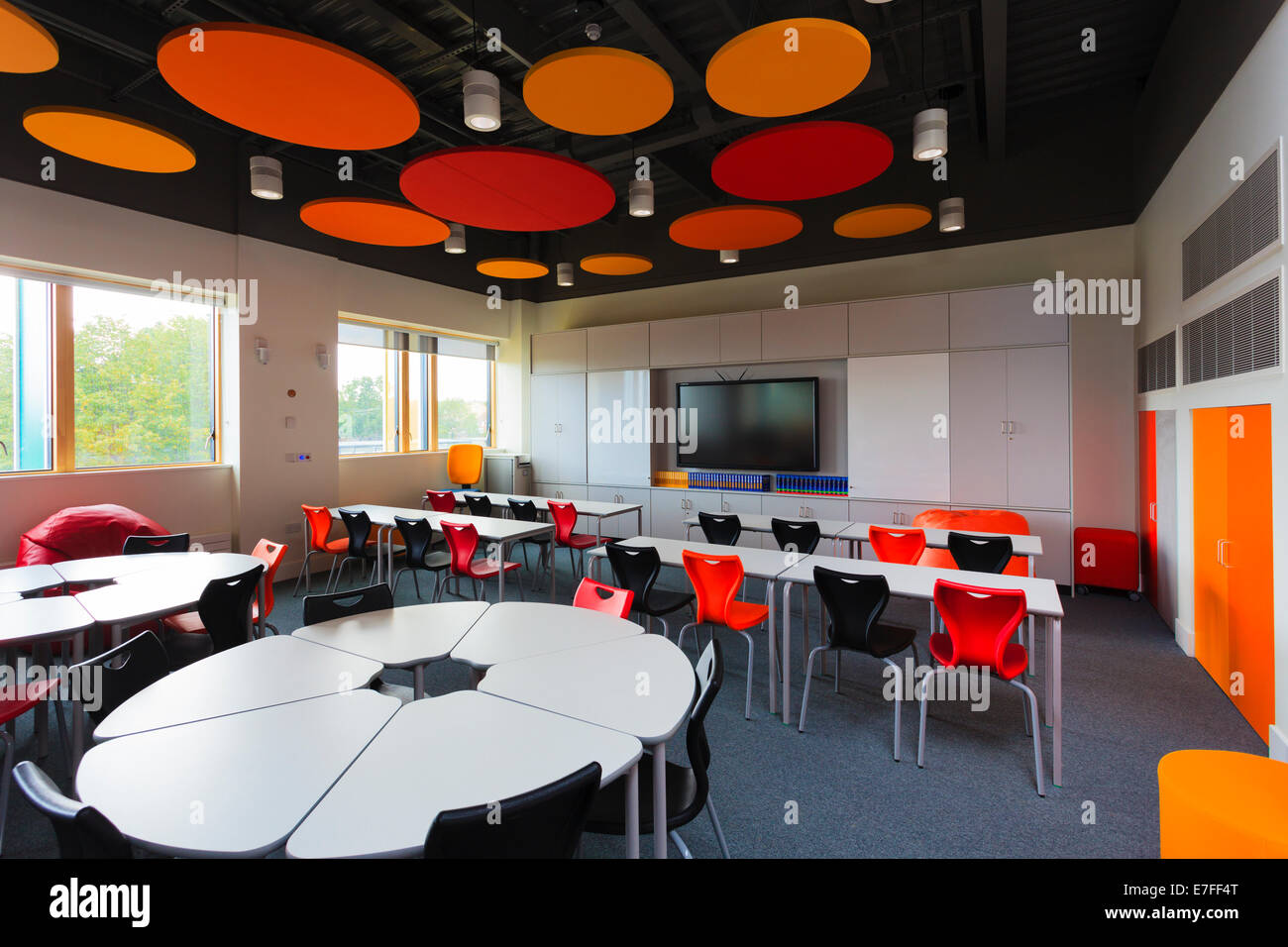 Unoccupied school classroom with colourful acoustic ceiling discs. - Stock Image