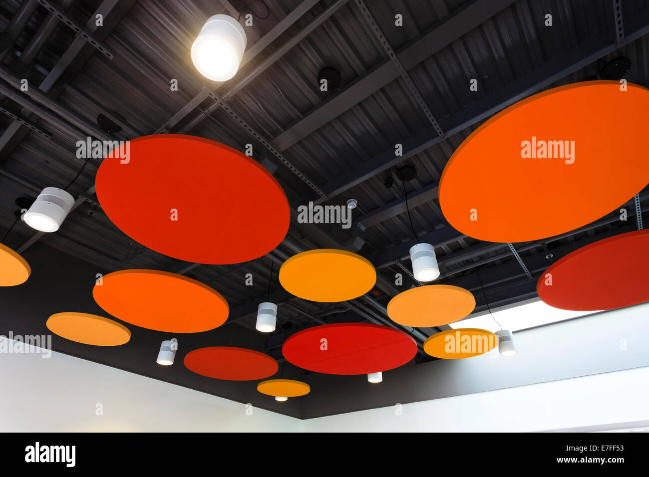 Colourful acoustic attenuator discs in ceiling. - Stock Image