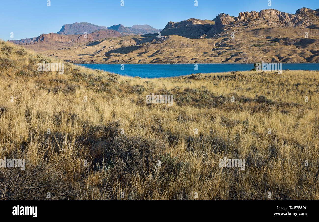 Buffalo Bill reservoir flanked by scrub land and rocky mountains at dawn near the town of Cody, Wyoming, USA - Stock Image