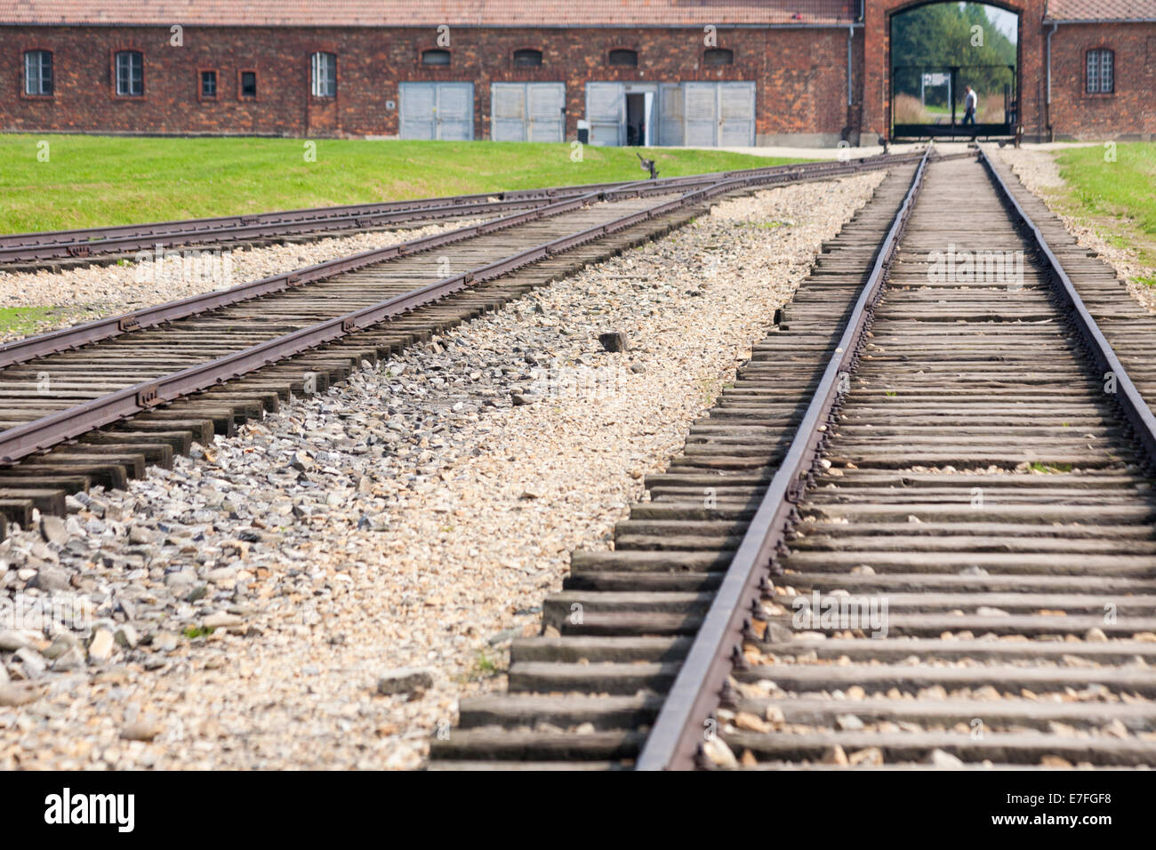 rail tracks leading to entrance gate at the Auschwitz-Birkenau concentration camp, Auschwitz, Poland - Stock Image
