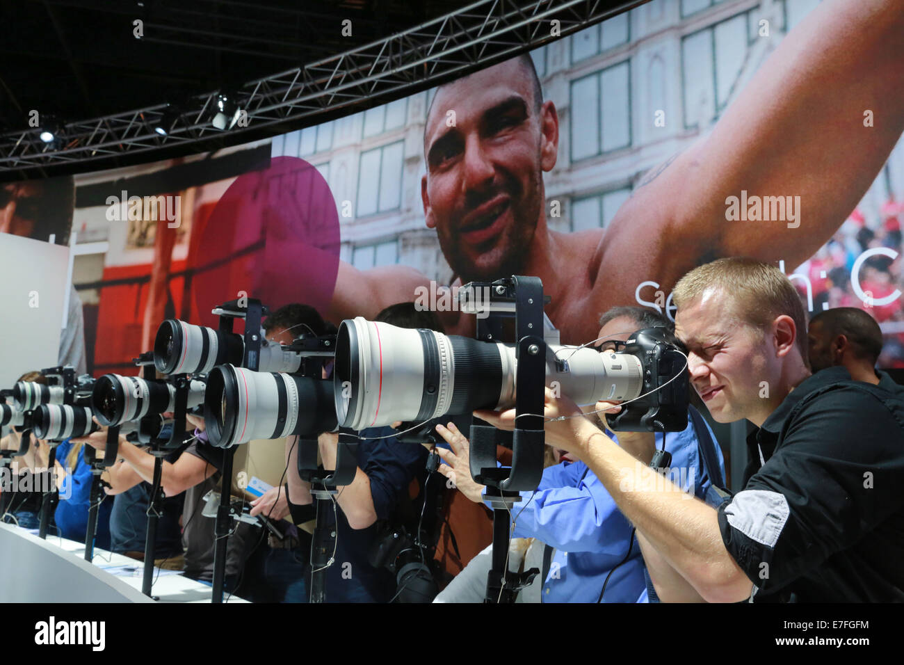 Photokina photography trade fair in Cologne, Germany. Visitors to the Canon stand try out a selection of large telephoto - Stock Image