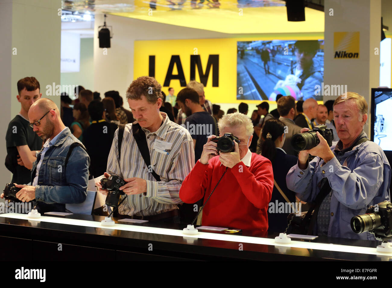 Photokina photography trade fair in Cologne, Germany. Visitors to the Nikon stand try out a selection of consumer - Stock Image