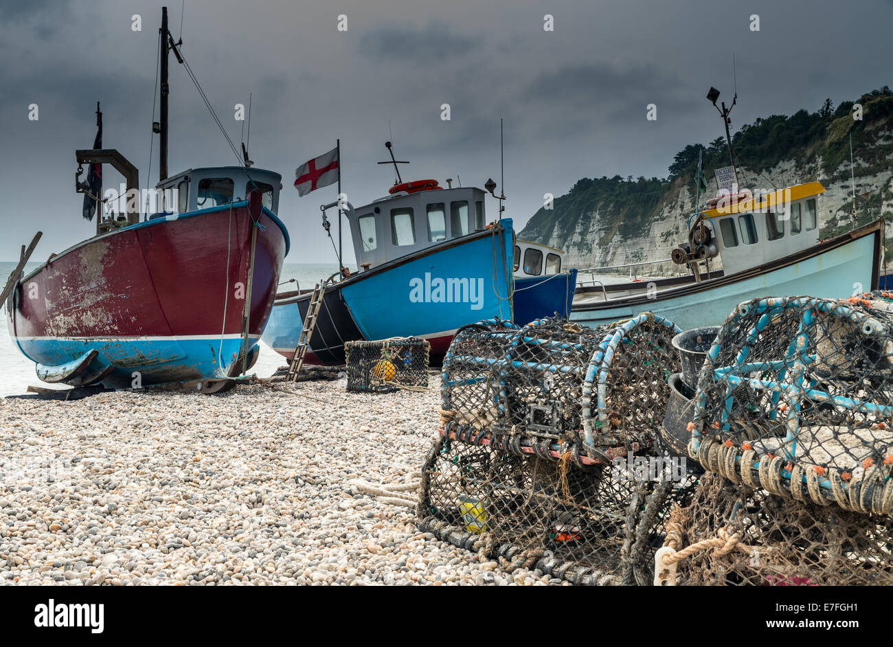 Fishing boats moored on the beach at Beer in Dorset, United Kingdom - Stock Image