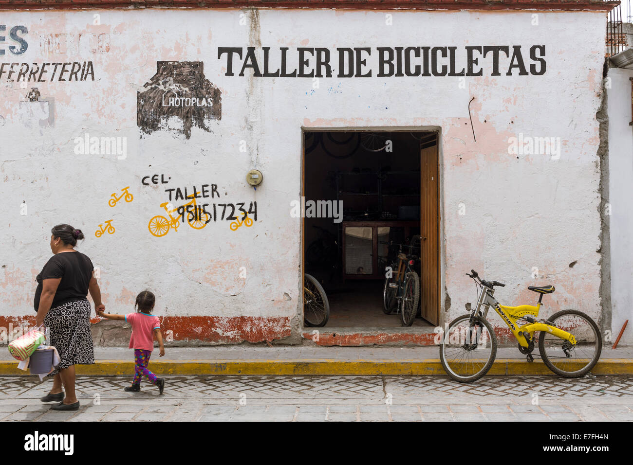 Mother and son passing by a bicycle repair shop in Mitla, Mexico - Stock Image
