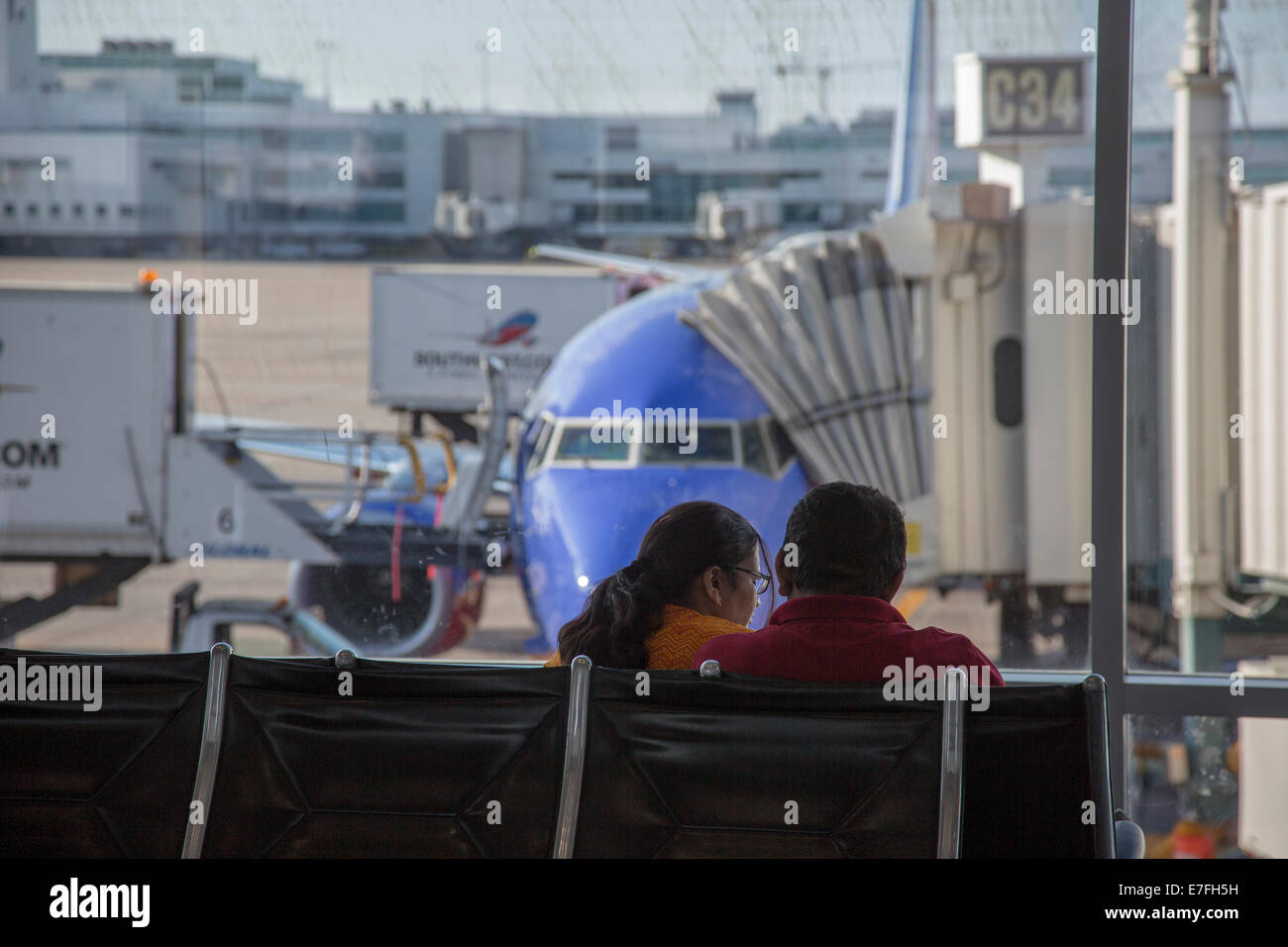 Denver, Colorado - A couple waits for their flight at Denver International Airport. - Stock Image