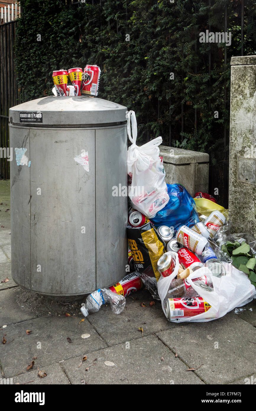 Overfull rubbish bin / garbage can with trash around and beer cans piled on top in city street - Stock Image