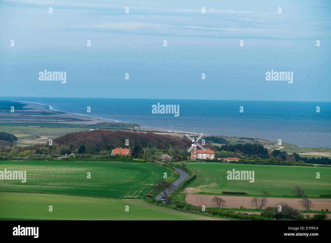 View of the North Norfolk coast showing Weybourne mill and shingle coastline. - Stock Image