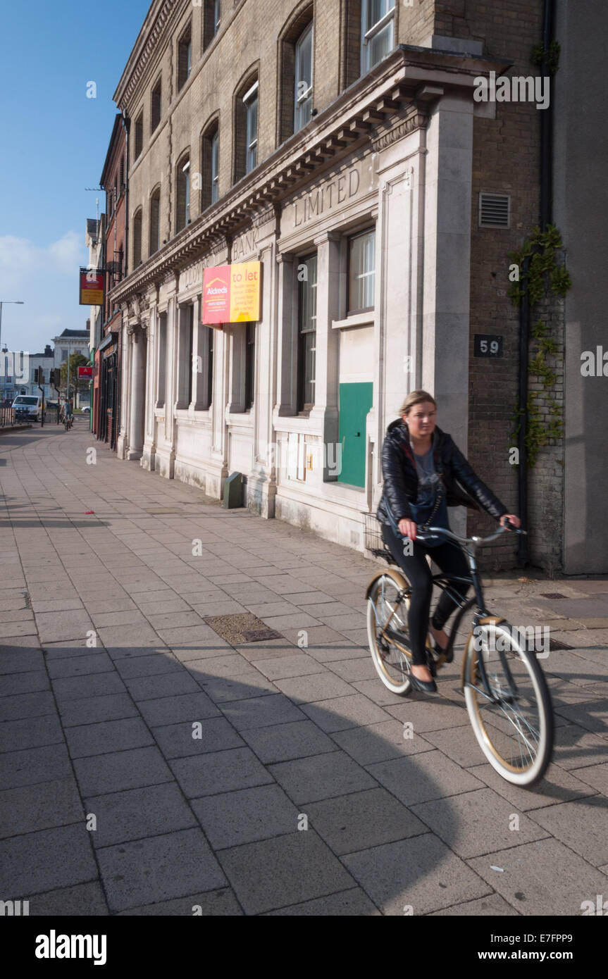 Cyclist passing the closed branch of Lloyds Bank in Great Yarmouth - Stock Image
