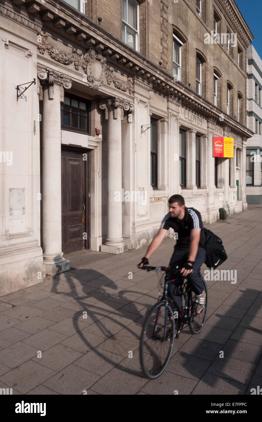 Cyclist passing the closed branch of Lloyds Bank - Stock Image