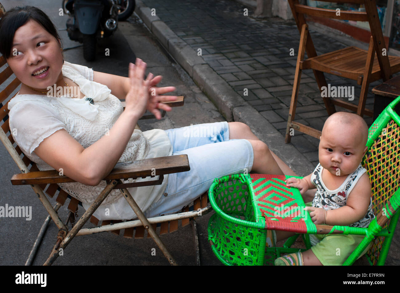 Mother take car of his children in the streets of Shanghai. Bringing children to live in Shanghai can create lots - Stock Image