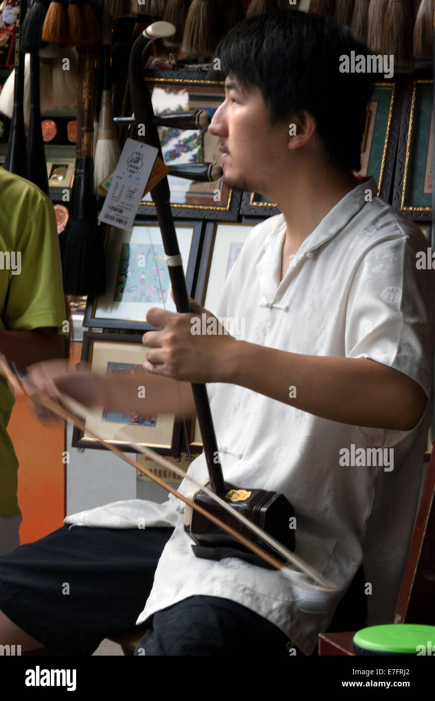 Playing traditional music instrument in Ancient Town of Shanghai. Stringed instrument called Sanxian. The sanxian - Stock Image