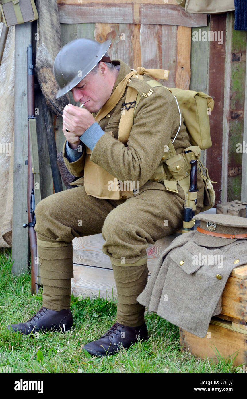 A military re-enactor in WW1 British Army uniform light s cigarette as he sits in a trench dugout display at Romsey - Stock Image