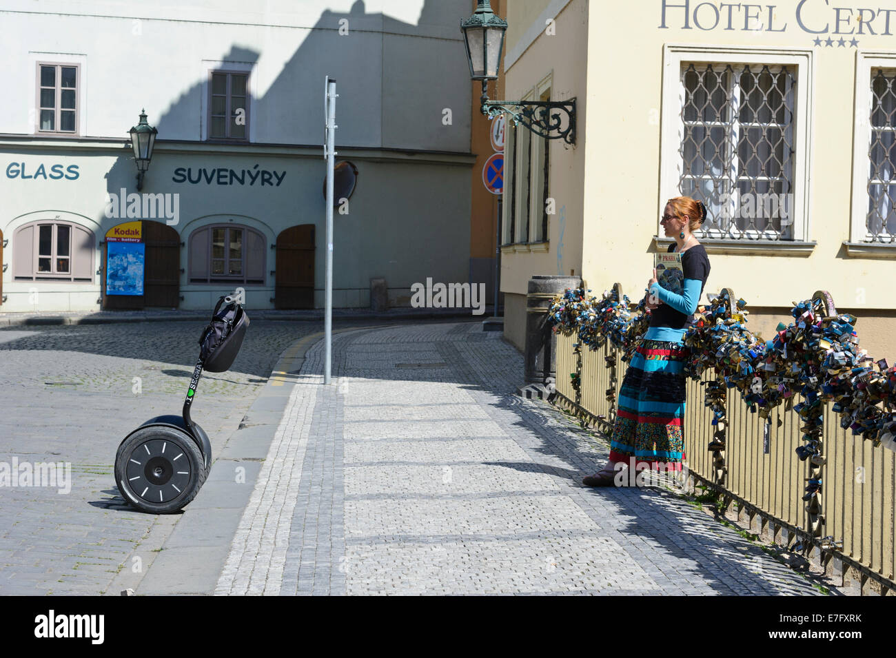 An agent of Segway leading against the railing of a bridge covered with a series of closed padlocks, Prague, Czech Republic. Stock Photo