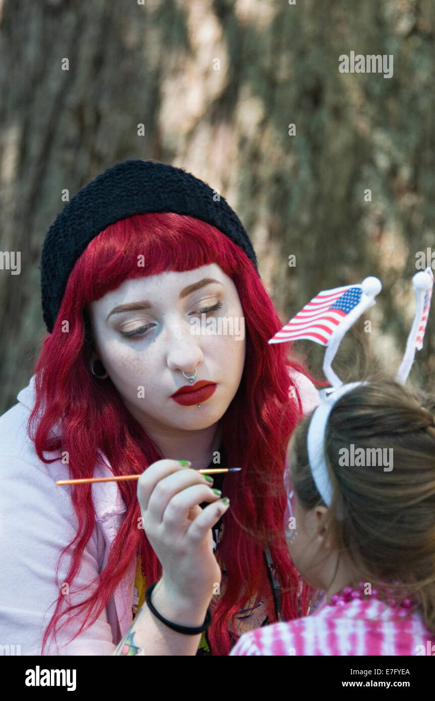 Young Woman Painting the Face of a Little Girl at Independence Day Celebration in New Pekin Indiana - Stock Image