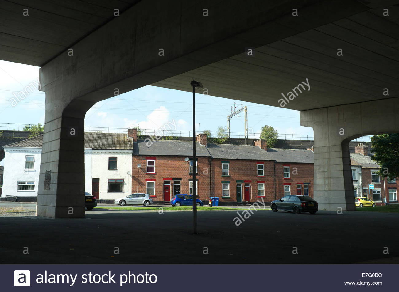 Old terraced homes, as seen from underneath a concrete flyover, in Runcorn, Cheshire, UK. - Stock Image