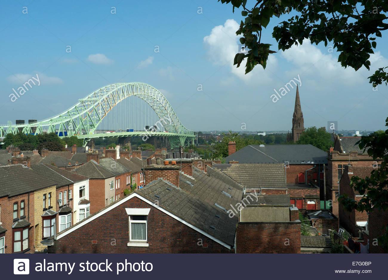 Properties in Runcorn, with the Runcorn - Widnes Bridge (Silver Jubilee Bridge) visible behind. Runcorn, Cheshire, - Stock Image