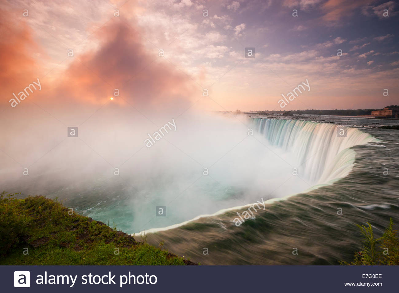 The rising sun shines through the thick mist generated by the force of Horseshoe Falls, one of the Niagara Falls - Stock Image