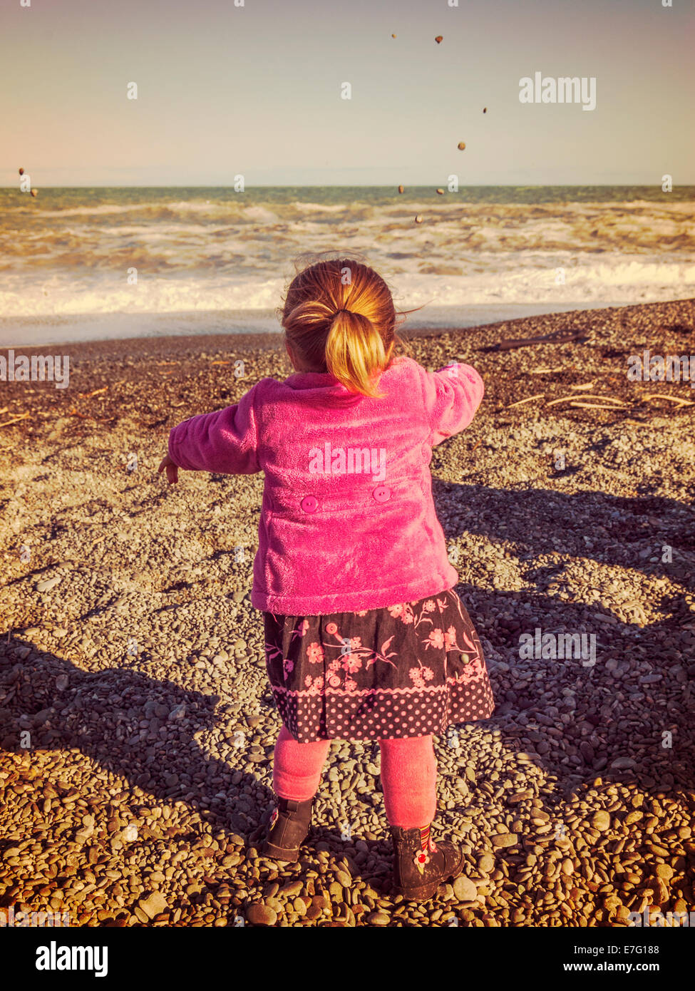 Little girl, 2 years old, throwing pebbles into sea, with instagram filter. - Stock Image