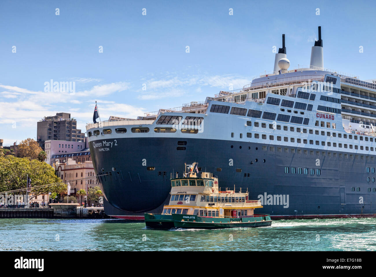 Cunard liner Queen Mary 2 berthed at Circular Quay, Sydney, and Sydney Ferry Charlotte. - Stock Image