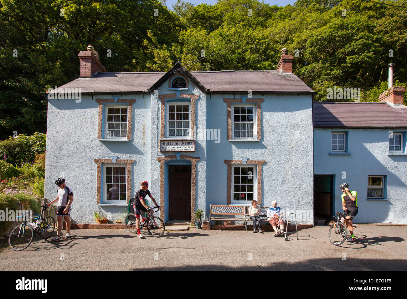Three cyclists prepare to leave a village pub in Pembrokeshire, Wales - Stock Image