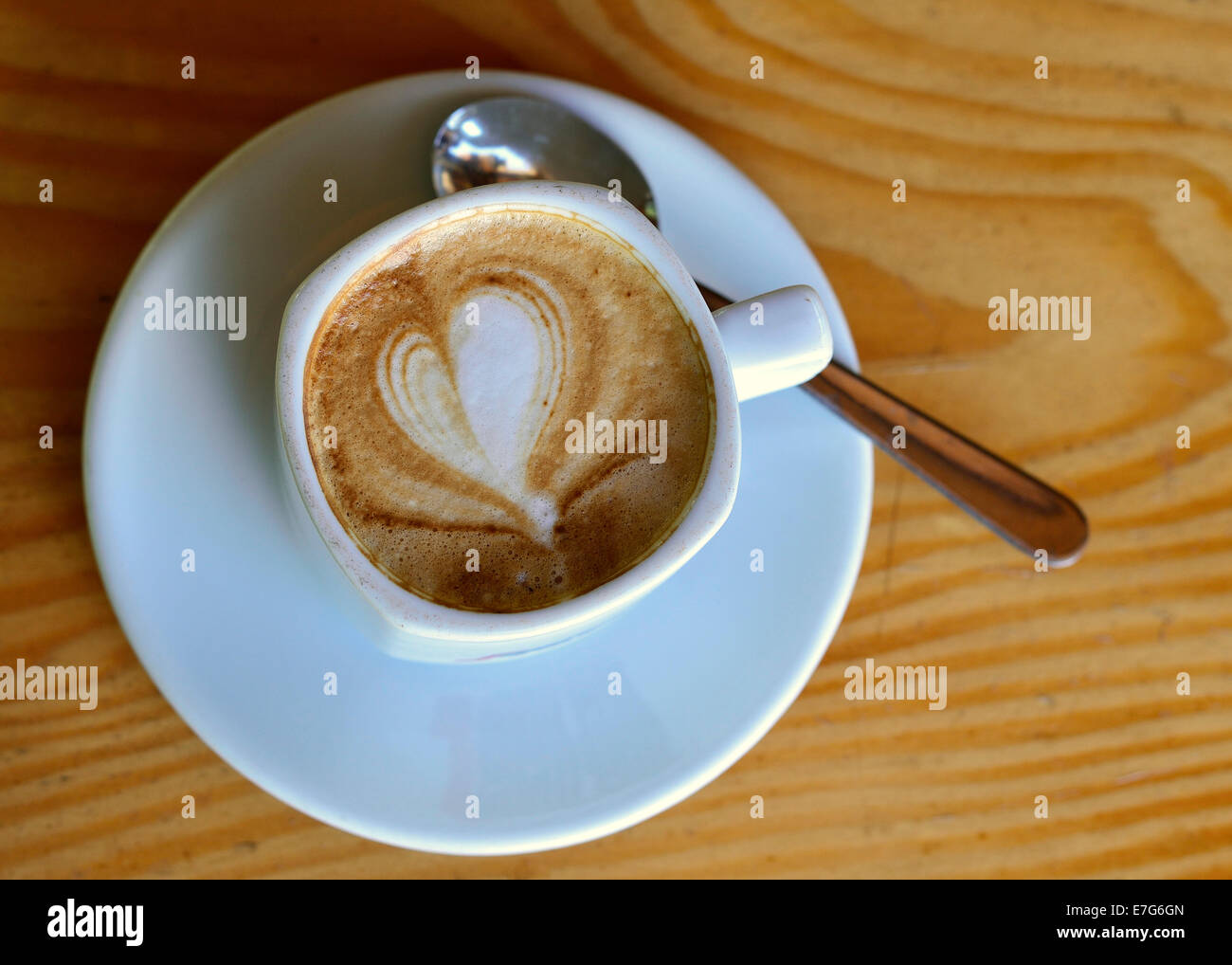Cup of cappuccino with milk foam in a heart shape - Stock Image