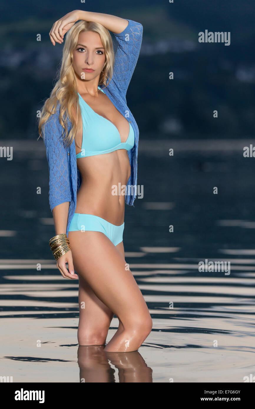 Woman wearing a light blue bikini standing in water - Stock Image