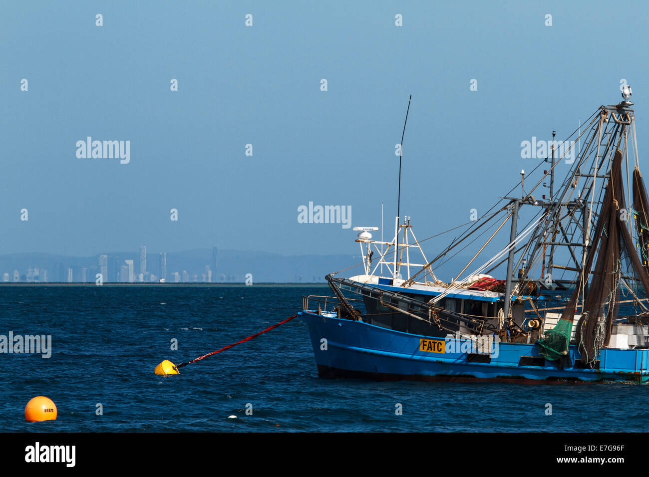 Trawler with Brisbane in the background - Stock Image