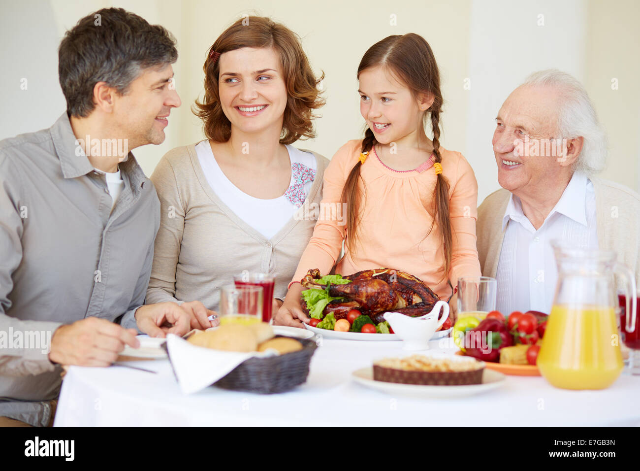 Big family looking at young man during traditional Thanksgiving dinner - Stock Image