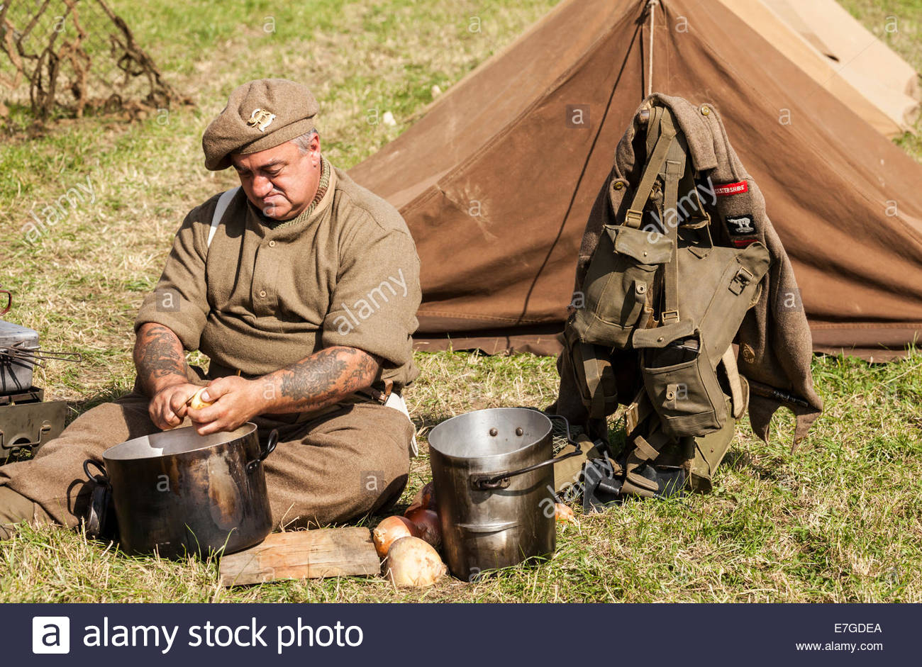 World War Two re-enactment.  British army soldier on kitchen duty peeling vegetables - Stock Image