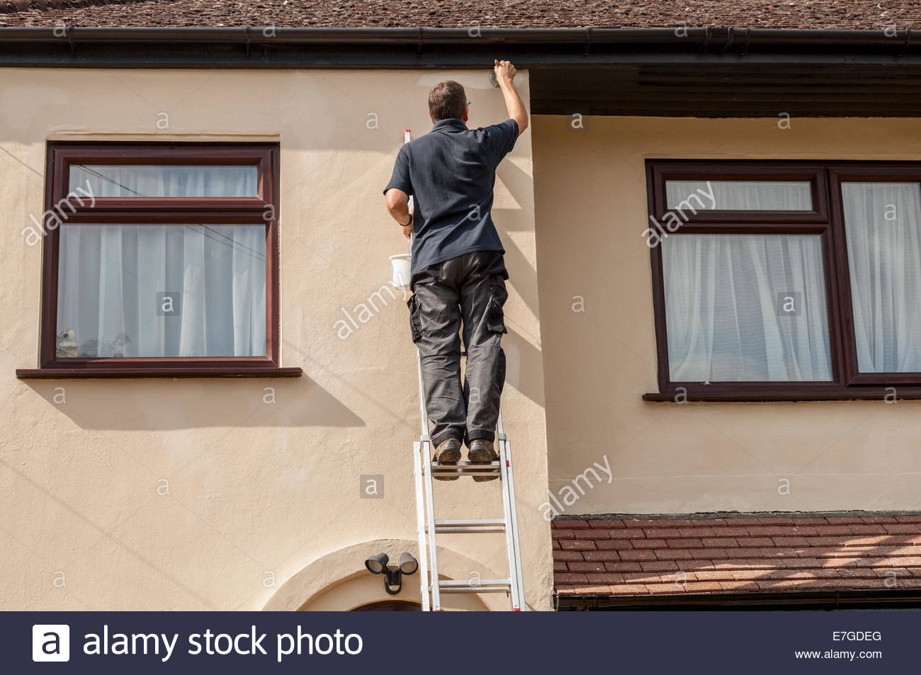 Man standing on a ladder painting house exterior Stock Photo