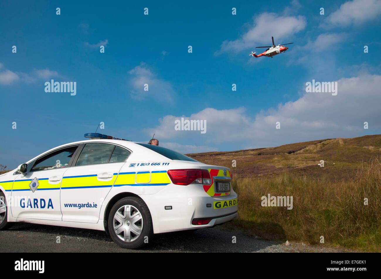 Irish Coast Guard IRCG  Garda Cósta na hÉireann Sikorsky helicopter flies above an Irish police car during a medical Stock Photo