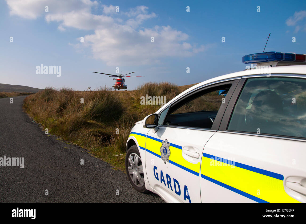 Irish Coast Guard IRCG  Garda Cósta na hÉireann Sikorsky helicopter flies above an Irish police car during a medical Stock Photo