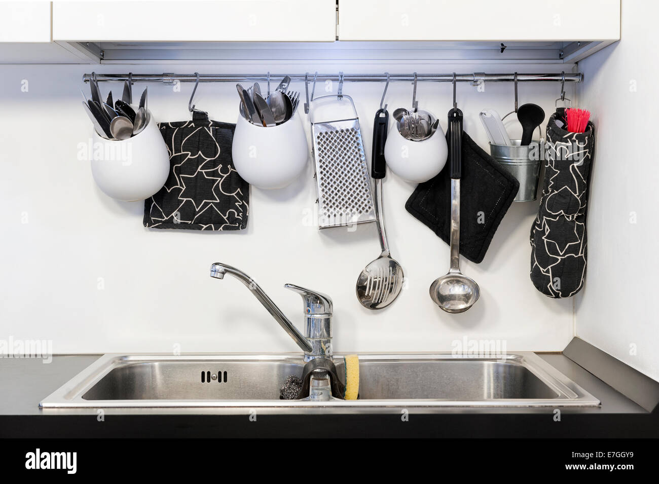 kitchen utensils hanging above the sink - Stock Image