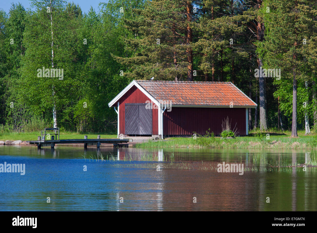 Red wooden boathouse along lake Siljan in summer, Dalarna, Sweden - Stock Image