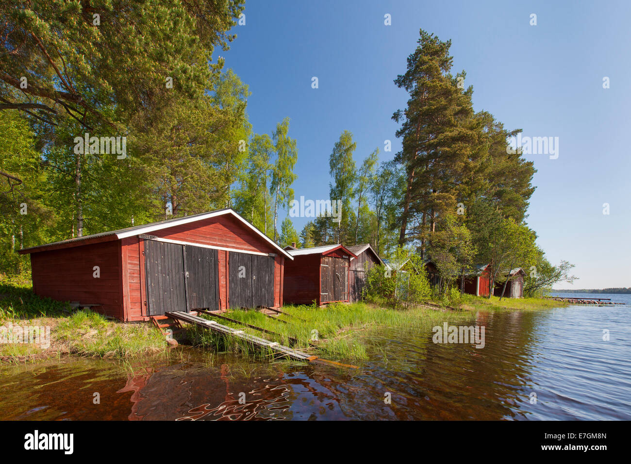 Red wooden boathouses along lake Siljan in summer, Dalarna, Sweden - Stock Image