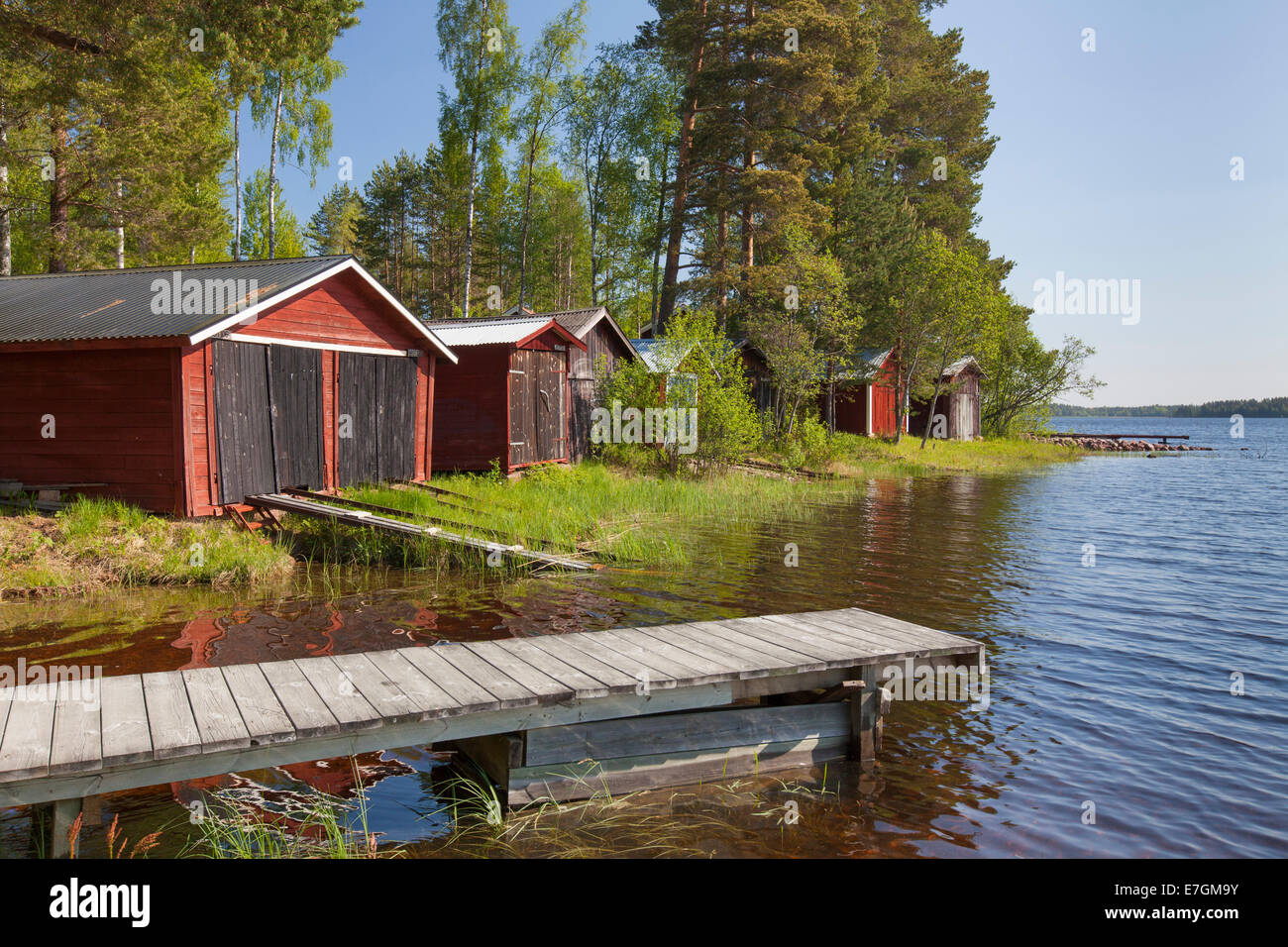 Red wooden boathouses along lake Siljan in summer, Dalarna, Sweden - Stock Image