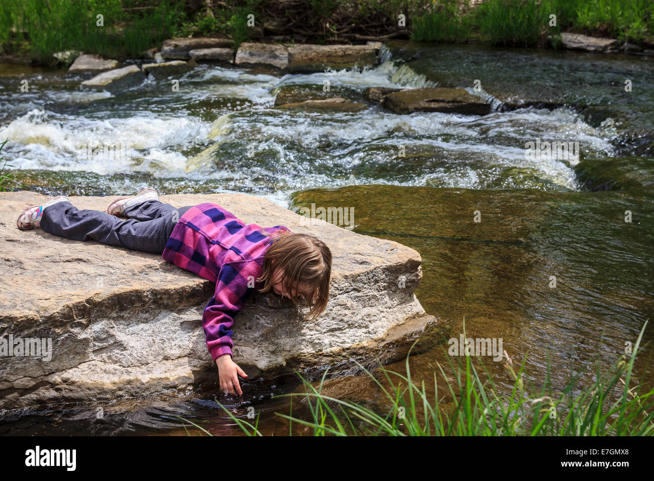 Young girl playing by a stream in the woods.  Tentatively dipping her hand in the water. - Stock Image
