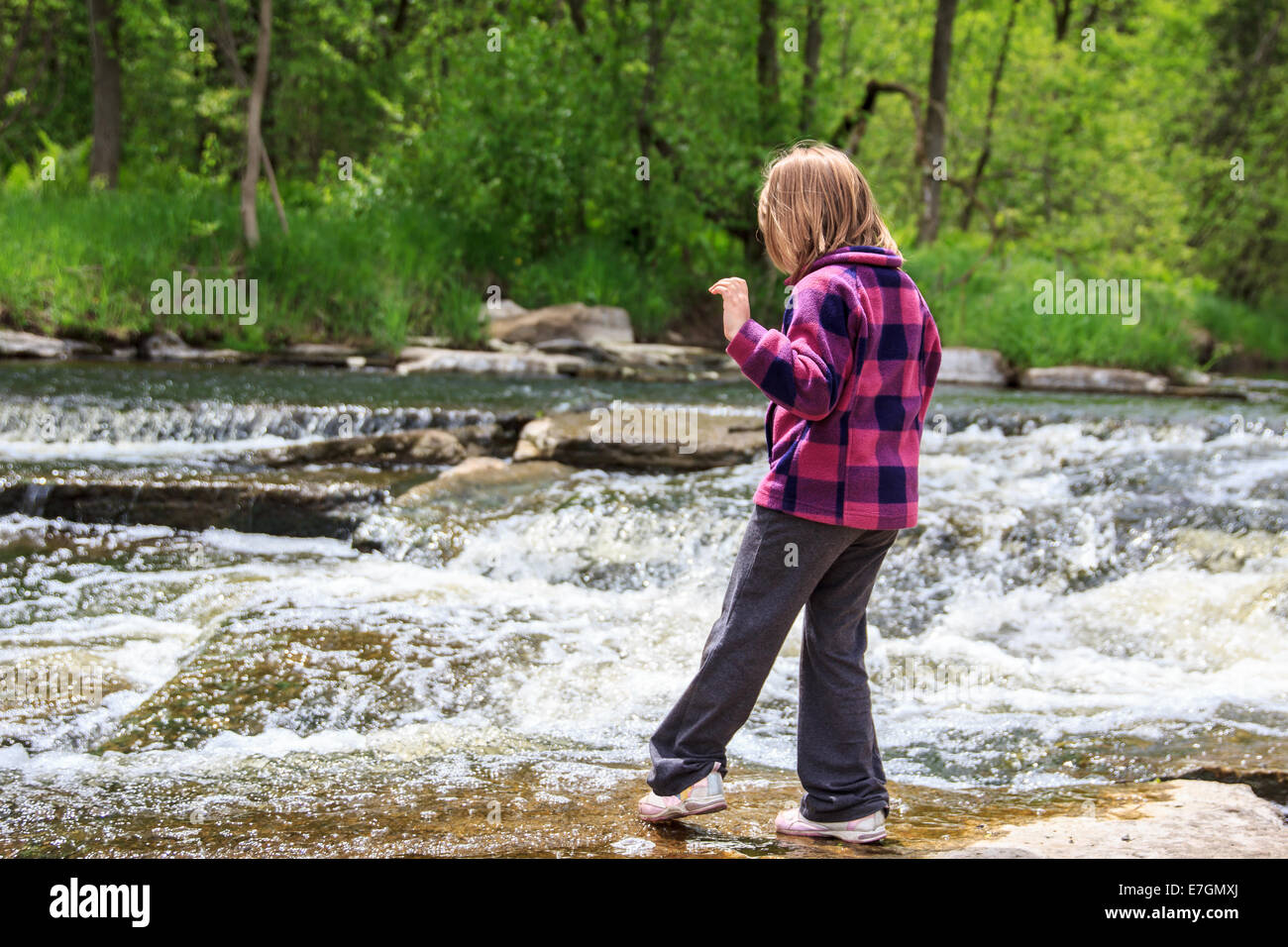 Young girl playing by a stream in the woods.  Tentatively dipping her toe in the water. - Stock Image