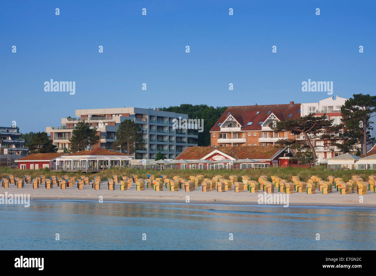 Roofed wicker beach chairs along the Baltic Sea at seaside resort Scharbeutz, Ostholstein, Schleswig-Holstein, Germany - Stock Image