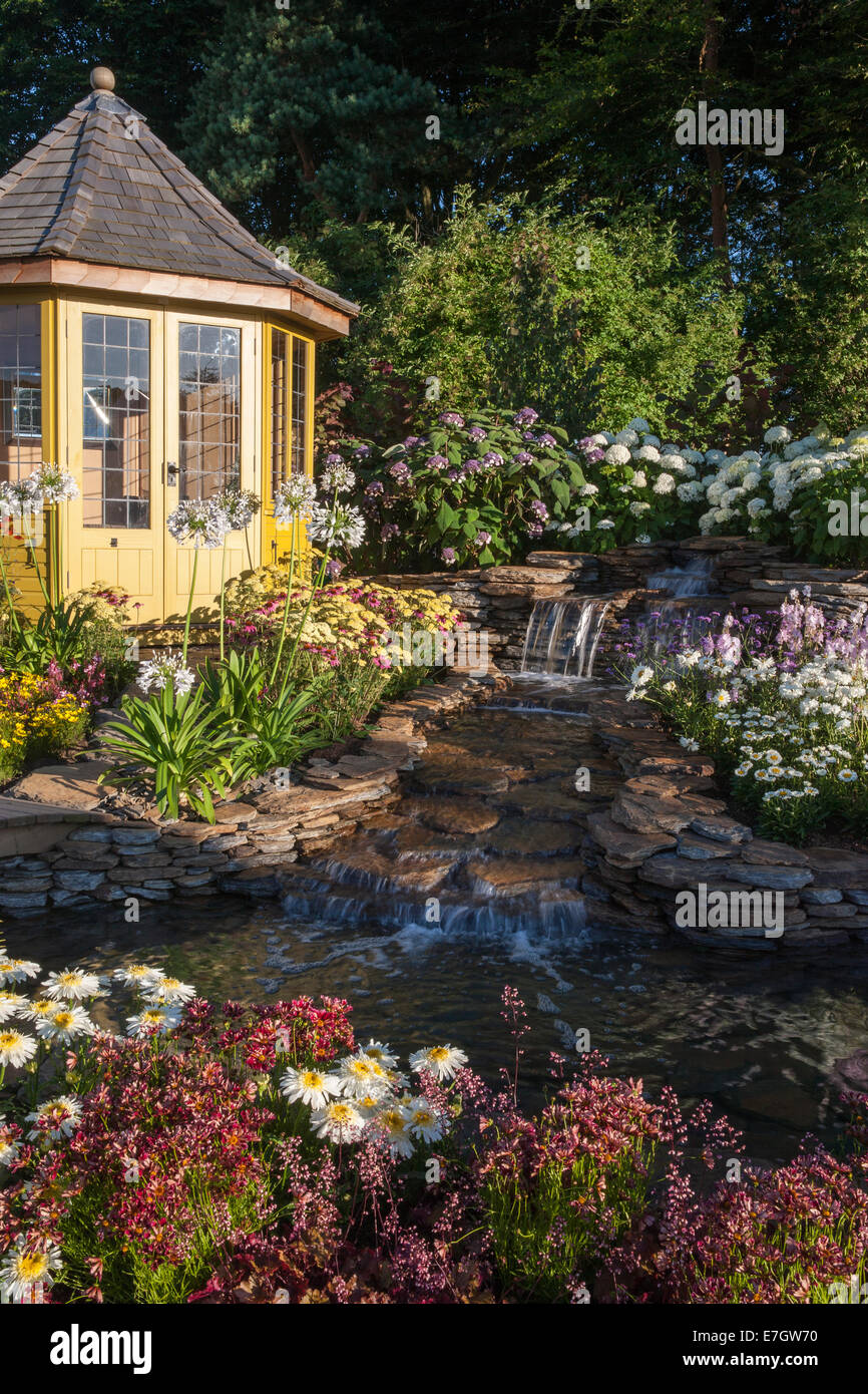 Garden - The Water Garden - summerhouse next to waterfall water feature planting Agapanthus 'Queen Mum' - Stock Image