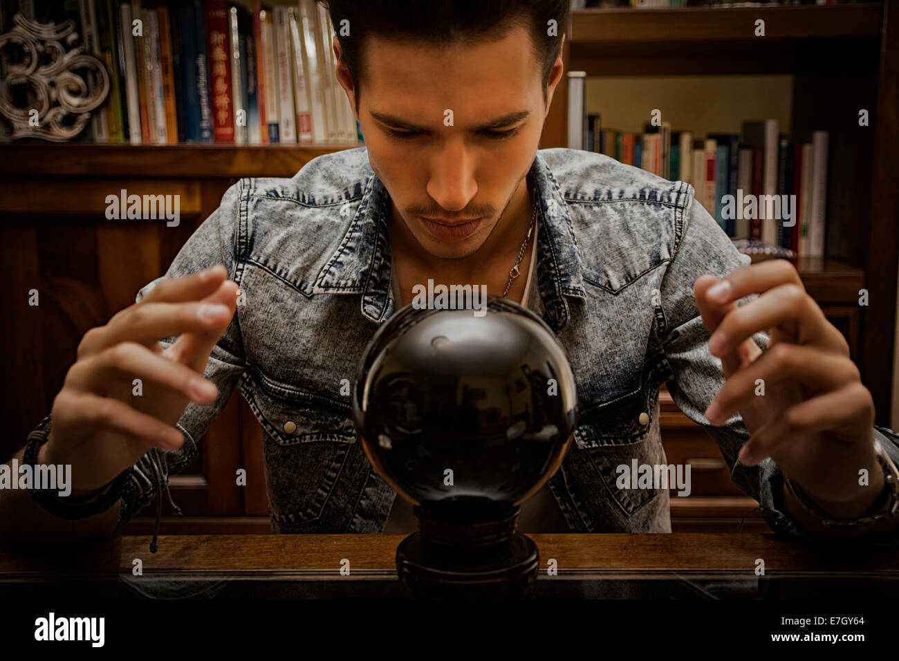 Handsome young man predicting the future by looking into black crystal ball - Stock Image