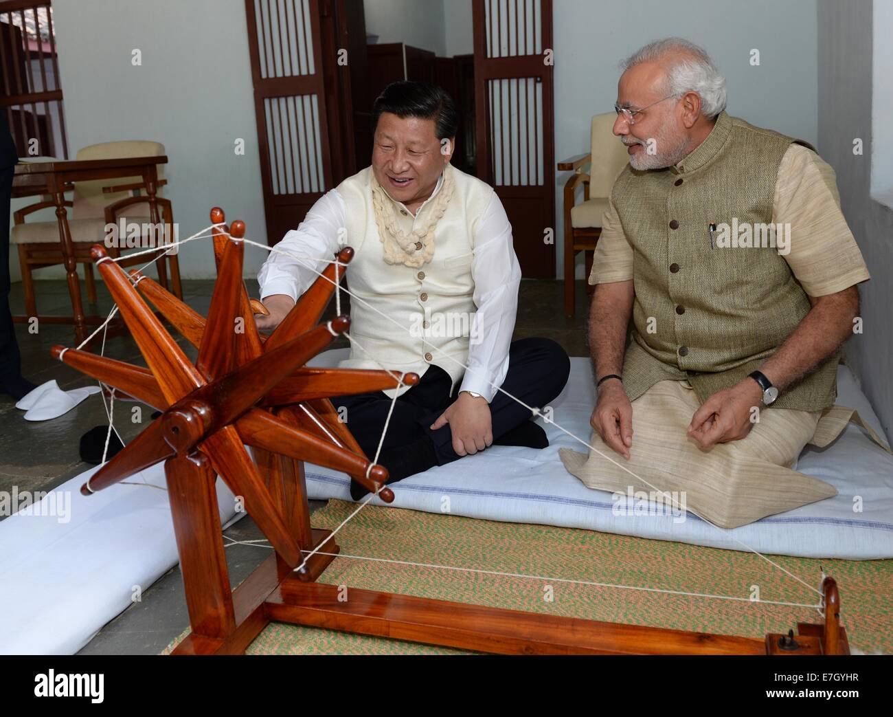 New Dehli, India. 17th Sep, 2014. Chinese President Xi Jinping (L) rotates a spinning wheel that was once used by - Stock Image