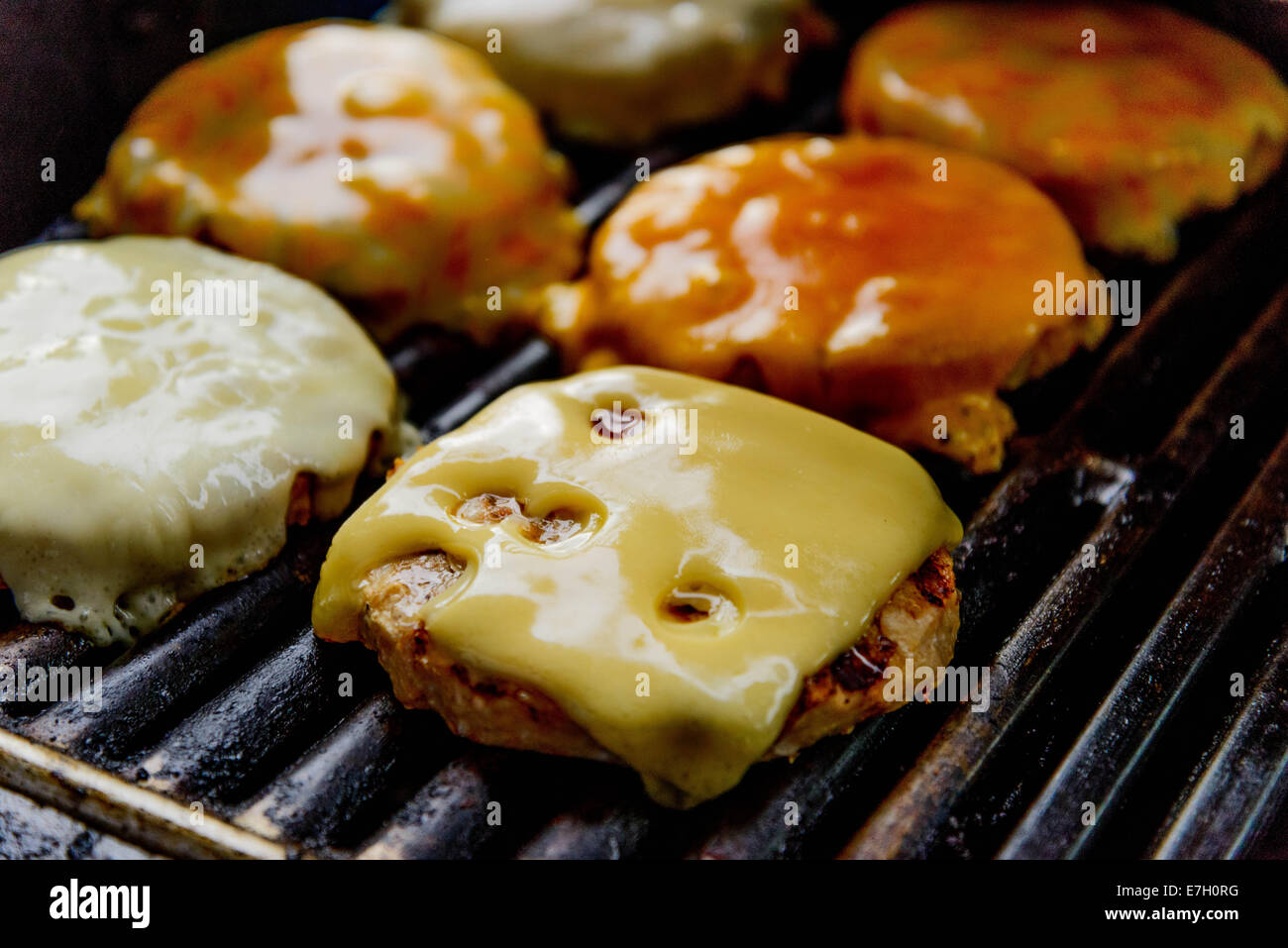 cheeseburgers cooking on the grill - Stock Image